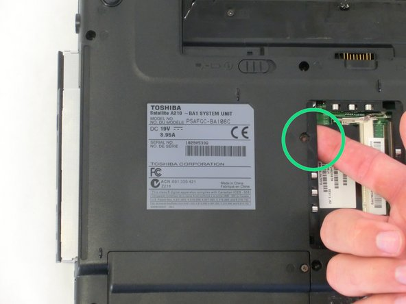 Using your index finger, push the metal tab inside the RAM bay which is located directly underneath the screw-hole.