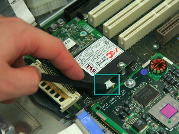 Image 2/2: Use the spudger to remove the modem cable as indicated.