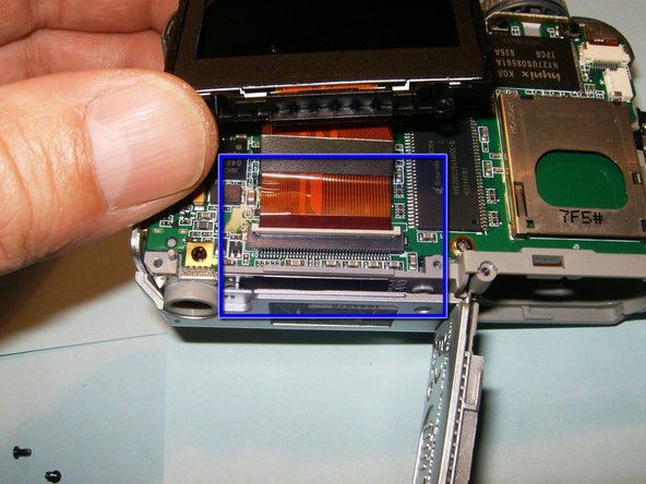 With the four screws removed, the connector for the LCD is easily accessed. Move the white clip in the opposite direction of the cable to open the connector.