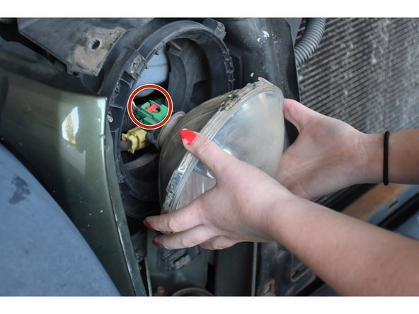 Locate red tab on the headlight plug connector, and push it away from the headlight.
