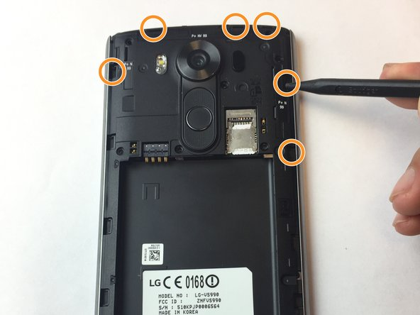 Use plastic tweezers to release the rest of the panel from plastic bits holding it in place and pry the panel up around the sides surrounding the fingerprint sensor and camera lens; set the back panel off to the side.