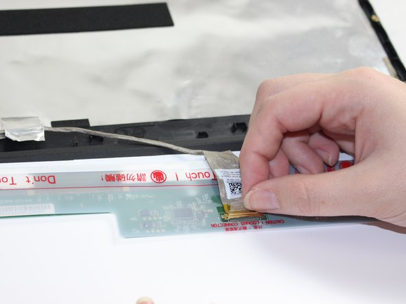 With the screen on the paper, detach the Zero Insertion Force (ZIF) connector  attaching the screen to the video cable inside of the front cover.