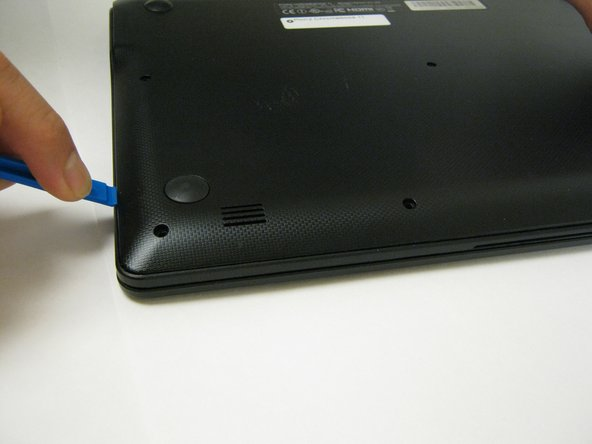 Insert a 1cm-wide plastic opening tool between the base and top frame.