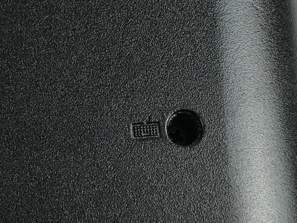 On the back panel of the laptop are two screws which have a keyboard symbol next to them.