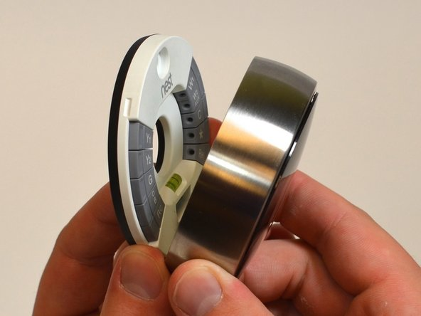 Grasp the display's metal outer ring with your fingers and pull directly away from the wall.