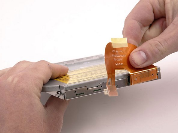 Peel the orange cable up from the top of the optical drive, removing tape as necessary, and disconnect it.
