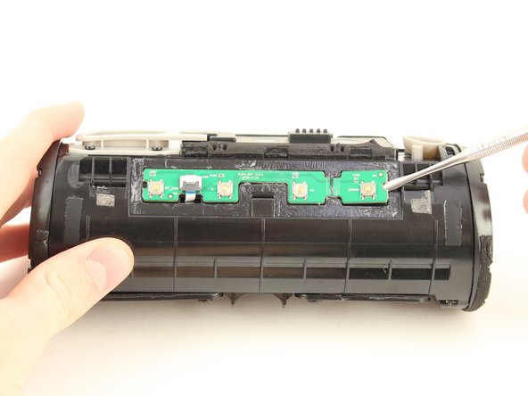 Pry up the button control board by inserting the metal spudger underneath both sides of the board.