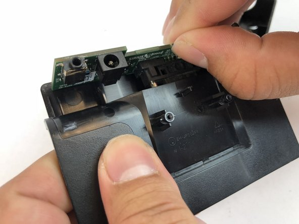 Once apart, lift the docking station motherboard up from the two pins that are located on the interior of the front casing.
