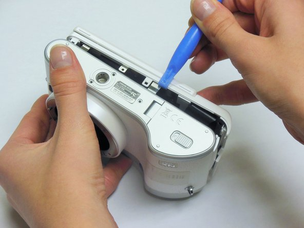 Place a plastic opening tool into the gap between the back panel and camera body, from both the top and the bottom of camera. Carefully pry open the camera and separate the back panel.