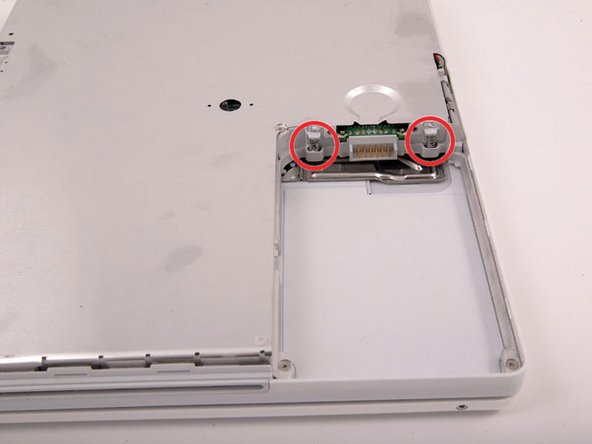 Image 1/1: Remove the small greasy springs with white plastic caps from either side of the battery contacts.
