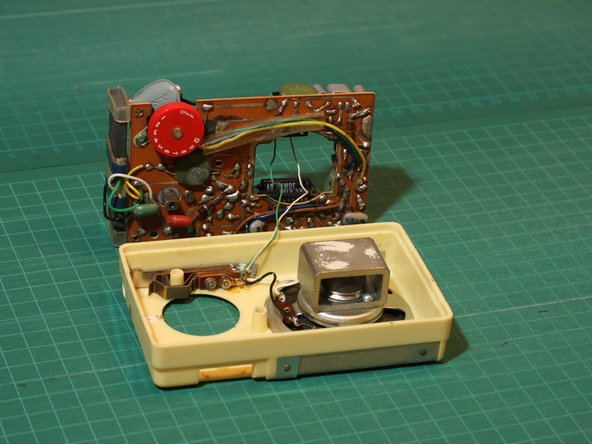 Set the circuit board beside the case, being careful not to damage the thin wires going to the earphone jack and speaker.