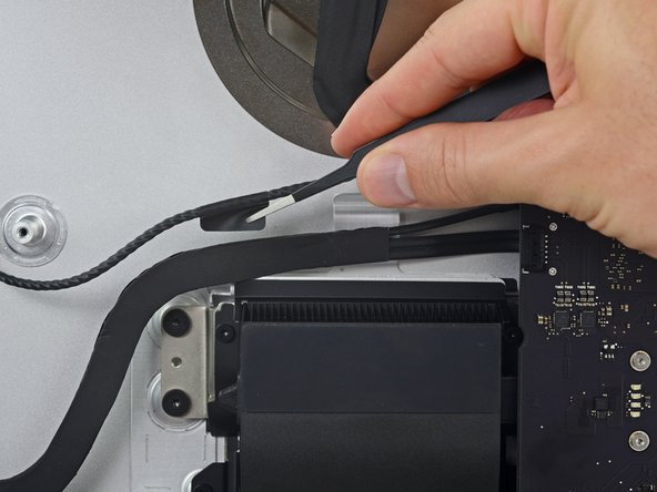 Peel up the piece of tape connecting the left speaker connector to the SATA power and data cables.