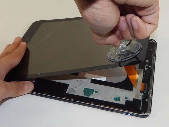 Place the small suction cup on the screen near the corner that the plastic opening tool is placed.