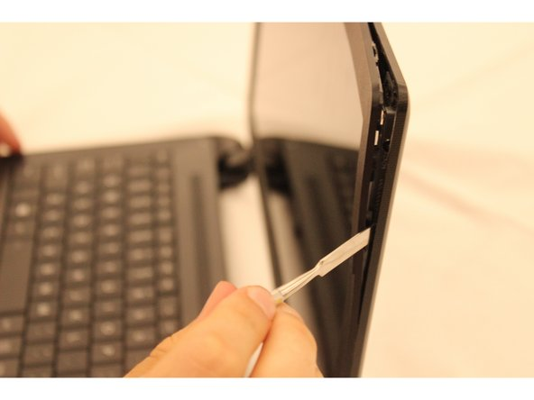 Slide the metal spudger down the side of the plastic screen casing until you hit a clip.