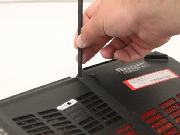 Using the black nylon spudger, carefully remove the rear cover from the laptop.