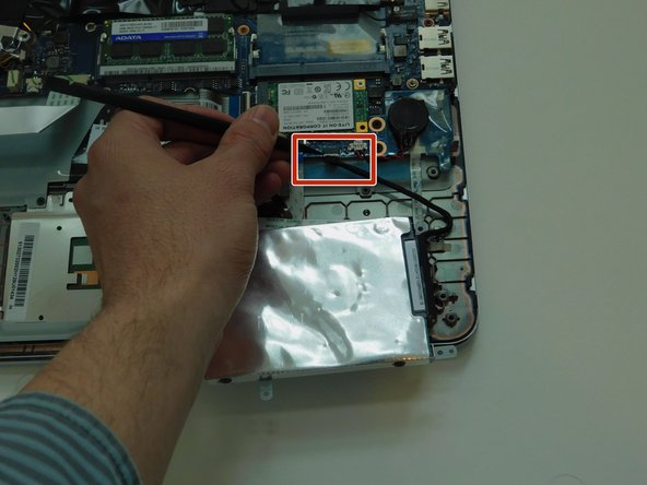 Use the plastic spudger tool to loosen the hard drive SATA cable connection by pushing it away from the motherboard.