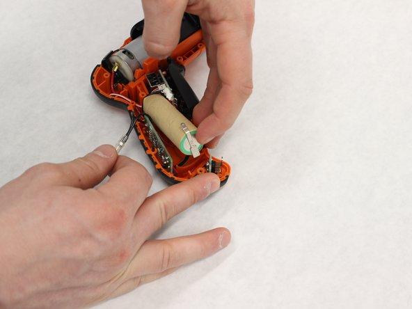 Gently lift the end of the battery out of the plastic casing