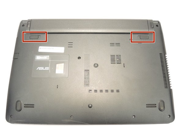 Image 1/2: Turn your laptop over, and press on the latches to remove the battery.
