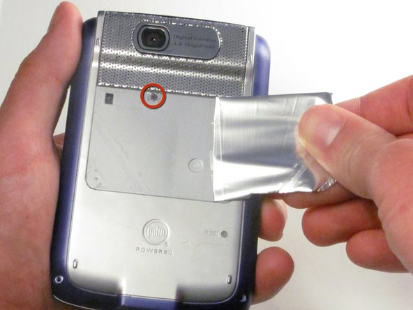 Peel back the adhesive label below the camera on the rear to reveal a hidden screw.