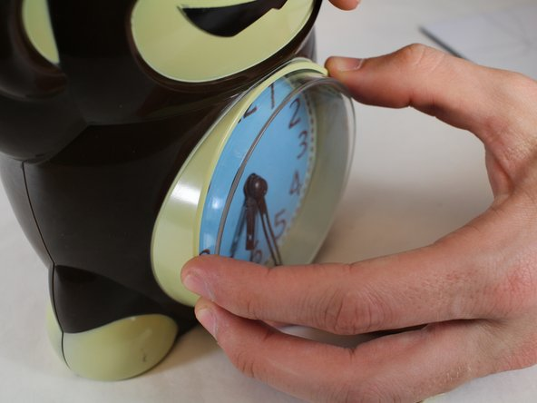 Grasp the plastic cover and carefully pull straight back so that the clock cover dislodges from its housing.