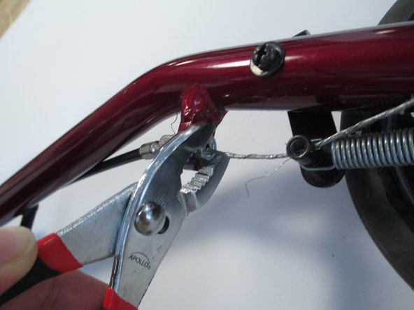 Use pliers or wrench to undo nut that secures the wire to the body of the walker