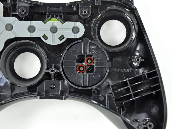 Remove the two 7.0 mm silver Phillips screws from the back of the D-pad.