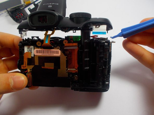 Use the opening tool to pry the top plate off of the top of the camera.