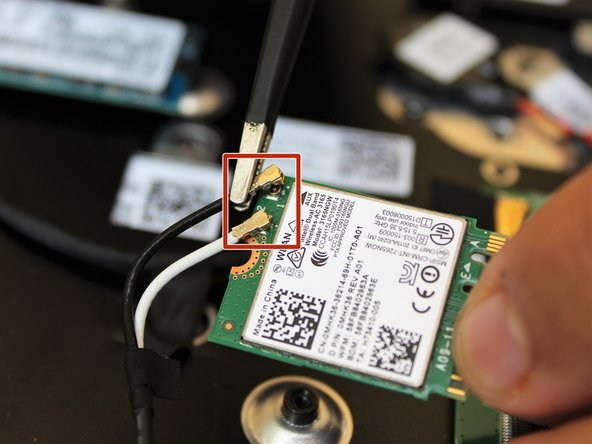 Remove the two connector pins from the wifi card using tweezers.