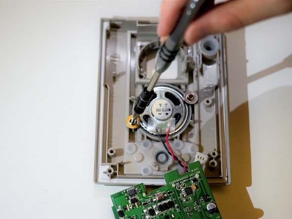 Gently lift the motherboard from the casing to reveal the speaker.
