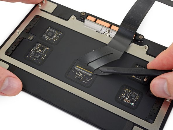 Carefully slide the edge of a halberd spudger or opening pick underneath the ribbon cable, and work the tool back and forth to separate the cable from the trackpad.