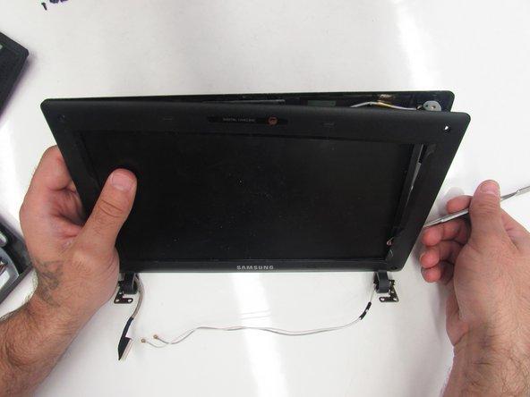 Apply pressure upwards to pop the screen bezel open.
