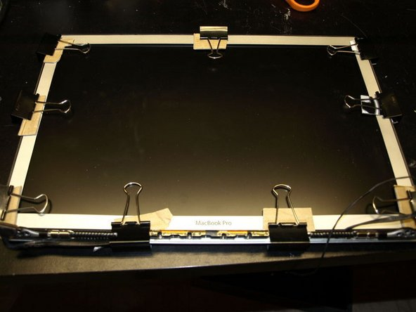 Place binder clips around the bezel to hold it in place. Use cardboard under the clips to keep from scratching the display assembly.