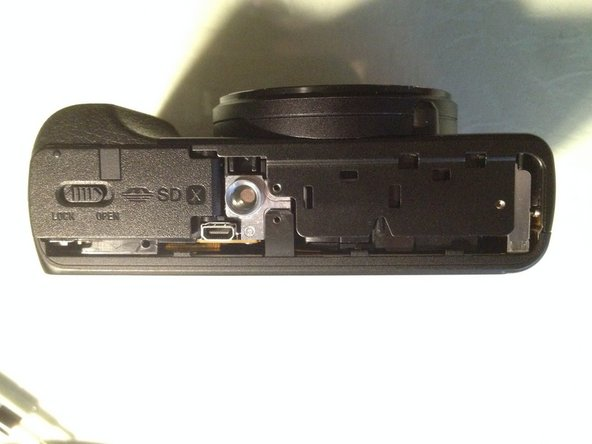 Pull the frame around the LCD  up from the bottom of the camera and remove it.