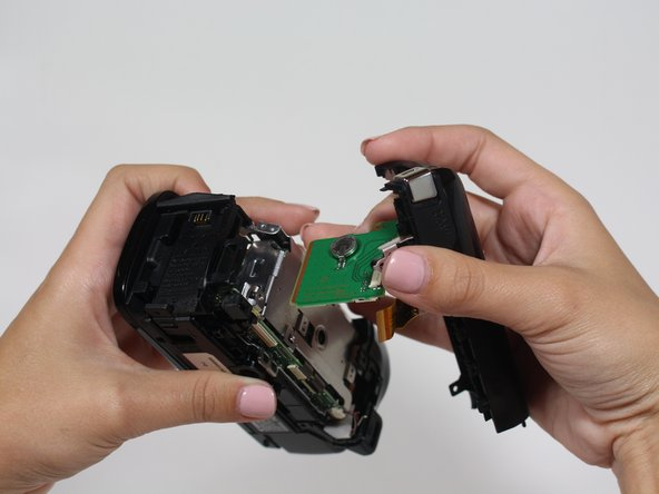 Pull the plastic casing away from the camera. The speaker and power button are housed in this casing.