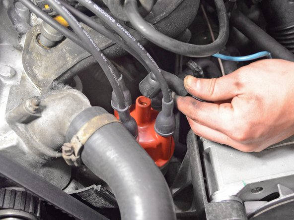 Image 2/2: Pull straight up on the ignition coil wire in the center of the distributor cap to disconnect it.