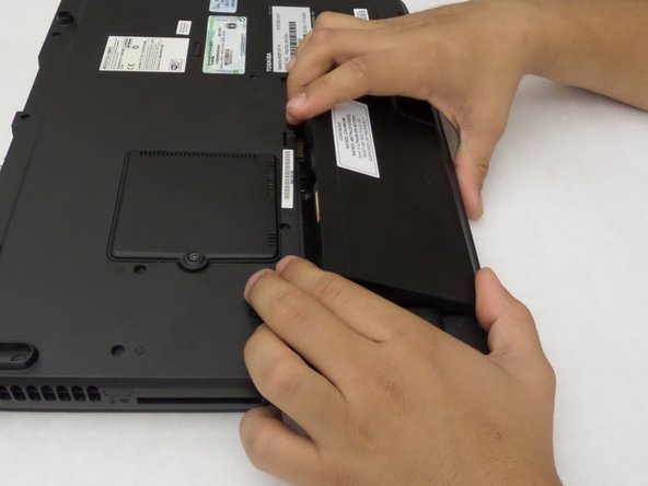 Image 2/2: Pull the battery out with your finger. Release the larger switch once the battery is out.