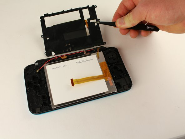 Using tweezers, pull up the plate covering the touchpad. The center ribbon cable will slide through this plate.