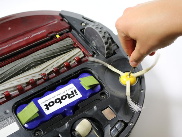 Using a flat head screwdriver, loosen the screw on the top of the side brush.