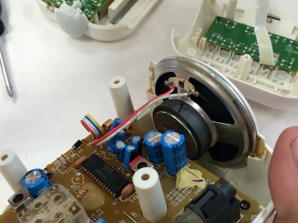 Place the new speaker in the slot and resolder the contact ports.