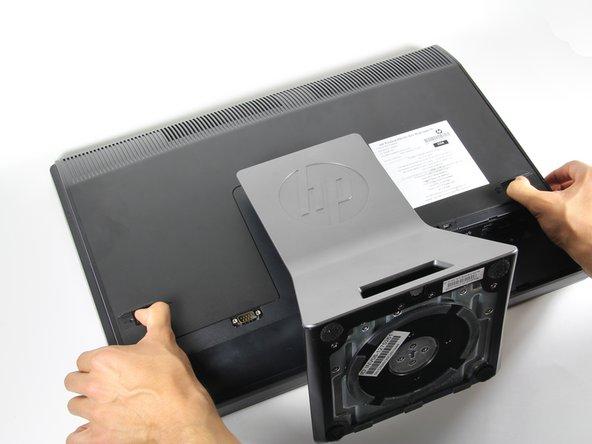 Empuje las lengüetas de desbloqueo en la parte posterior del monitor hacia dentro y hacia el otro mientras desliza la cubierta posterior hacia arriba.