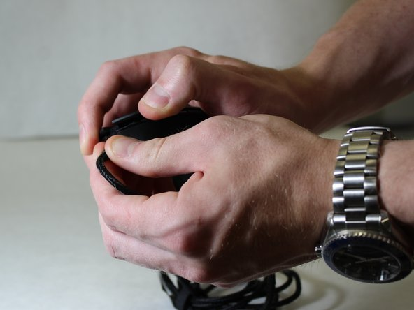 Grip the mouse cable with one had and the top buttons with the other and apply force in opposite directions to separate the two halves of the mouse.