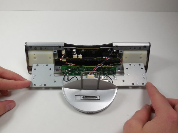 Using the plastic opening tool, remove the metal plate from the main speaker by gently pulling on it.