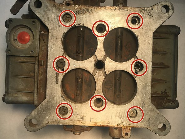 Remove the eight 20 mm Phillips screws from the bottom plate of the carburetor.