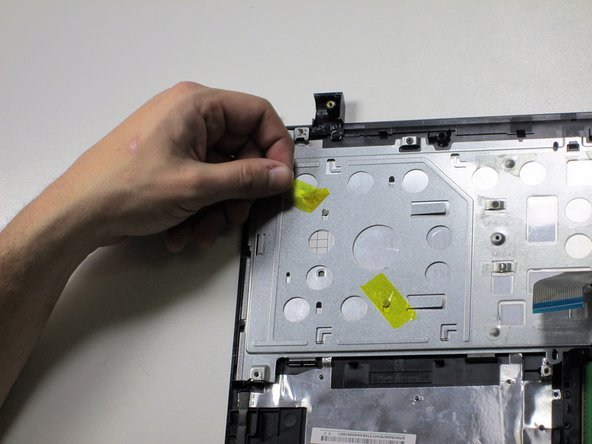Separate the top panel from the rest of the laptop.