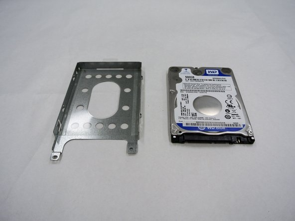 Remove the two 9.0 mm screws on each side of the silver box to slide the hard drive from the silver box housing.