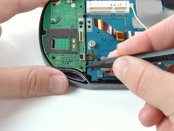 Use a spudger to free the right button board by prying up from the bottom right corner of board.