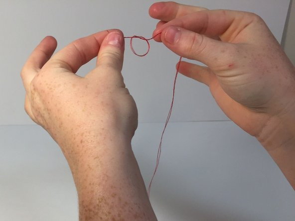 Pull the thread through the needle so that there is an equal length on each side of the needle.