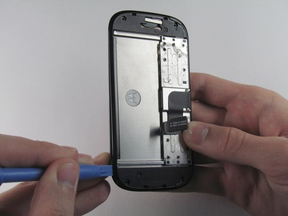 Run the plastic opening tool along the edges to separate the black plastic cover from the display assembly.