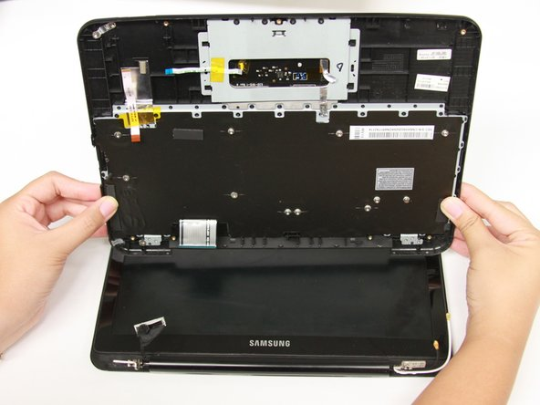 Pull the keyboard and trackpad away from you to detach them from the spine of the Chromebook.