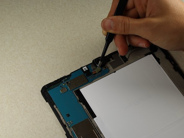Using the tweezers, remove the green protective film from the connector between the rear camera and the motherboard.